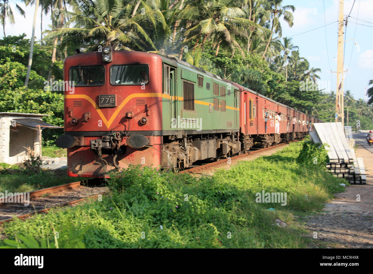 A train passing some coconut palm trees on it's way to Colombo, Sri Lanka Stock Photo
