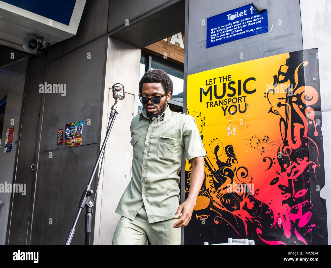 Afro busker singer musician performing in front of a poster saying Let the music transport you at the entrance of Brixton Underground station in South - Stock Image