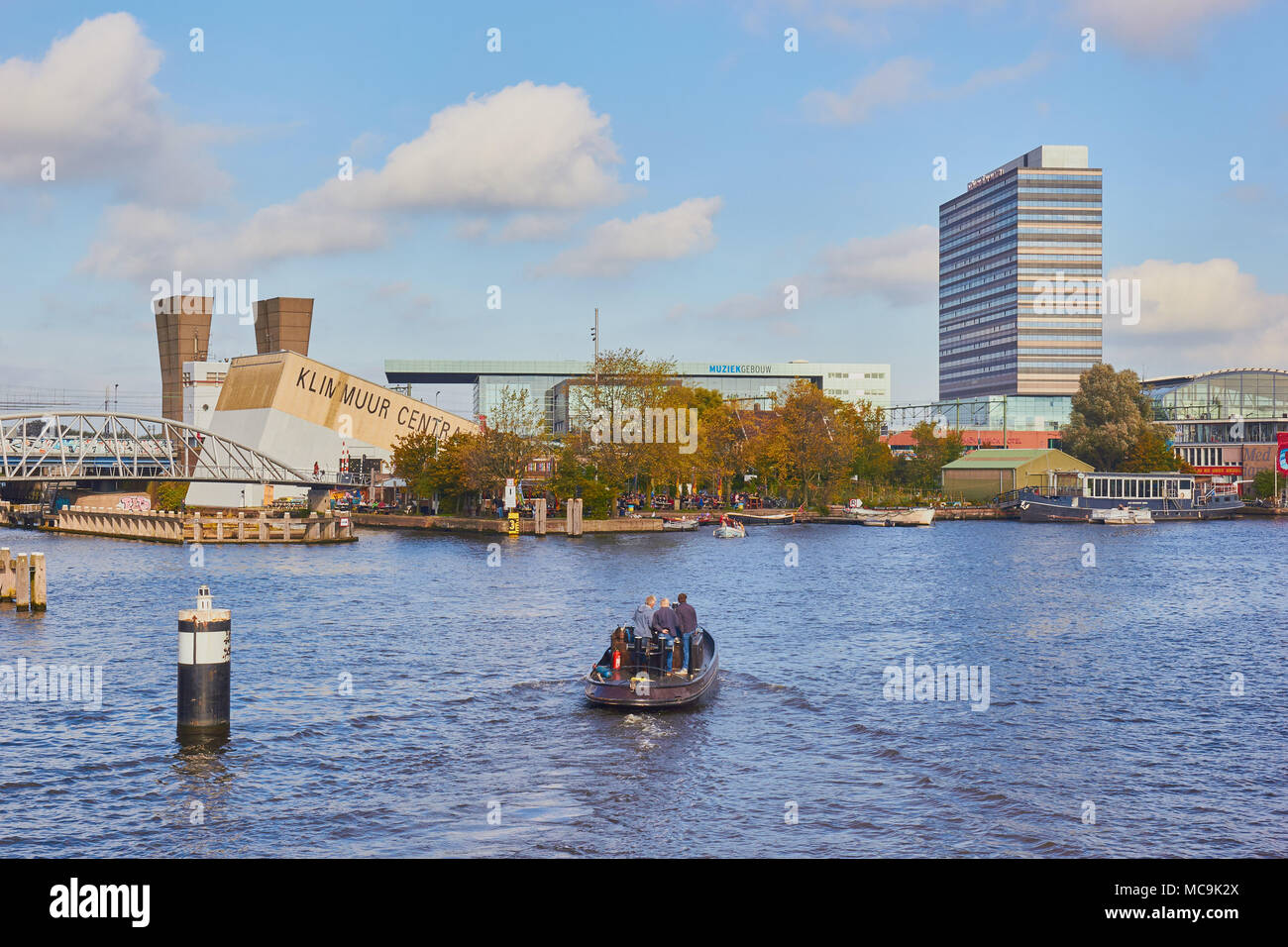 Boat on canal in the Oosterdokseiland (eastern docklands), Amsterdam, Netherlands - Stock Image
