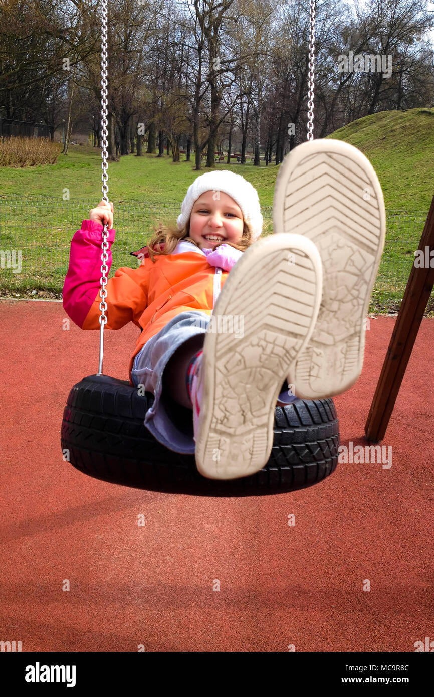 Happy child girl swinging on a playground in an autumn park. - Stock Image