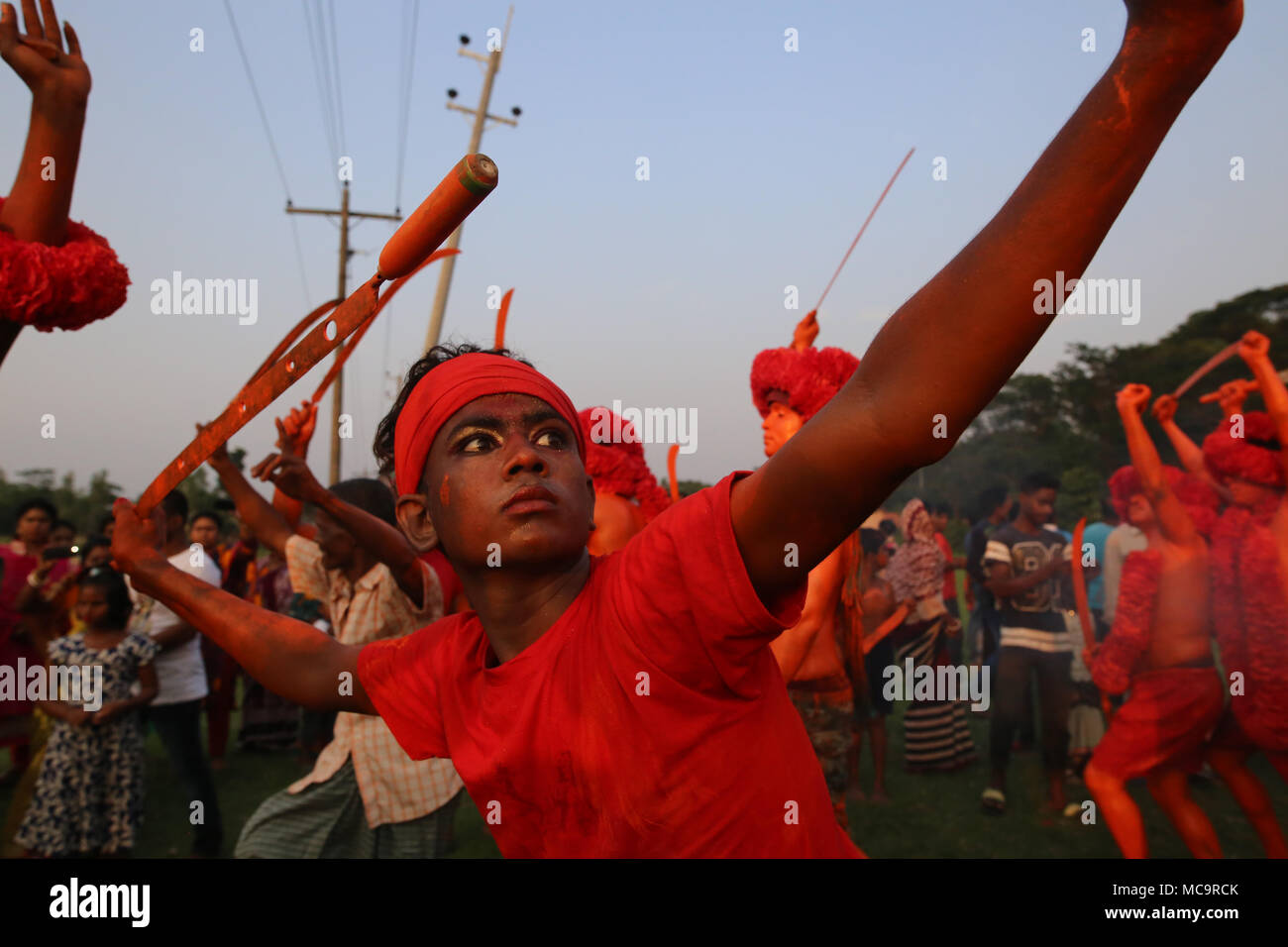 Dhaka, Bangladesh. Hindu devotees take part in lal Kach festival during the last day of Bengali month in Munshigonj, near Dhaka, Bangladesh on April 13, 2018. The festival is well known for the local community for more than hundred years. The Hindu youth and men paint themselves with red color and attend a procession holding swords as they show power against evil and welcome the Bengali New Year 1425 on 14 April 2018. © Rehman Asad/Alamy Stock Photo Stock Photo