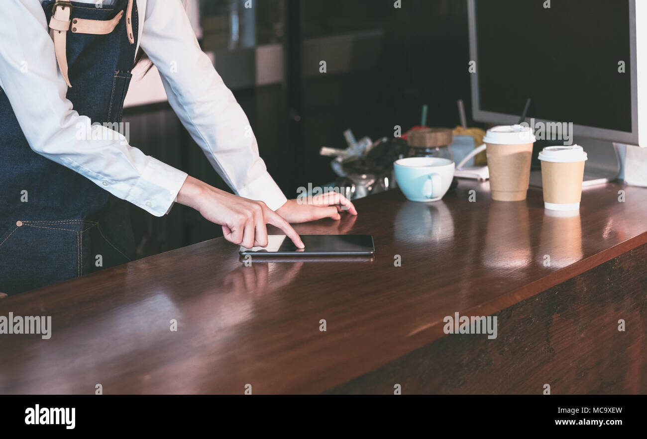 close up  barista waitress wear jean apron using tablet on counter bar to check stock in coffee shop.food and drink business.technology lifestyle - Stock Image