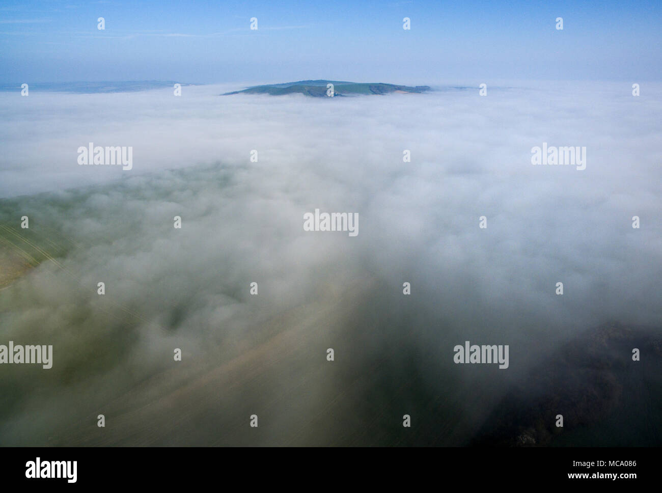 Firle, East Sussex. 14th April 2018. The South Downs emerge from low lying morning mist covering the Low Weald on a bright spring morning. © CAP/Alamy Live News Stock Photo