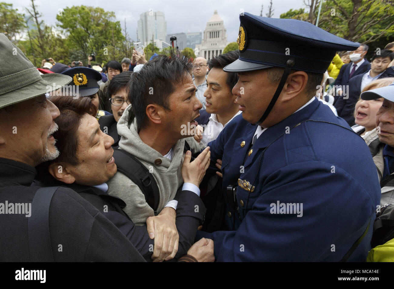 Tokyo, Japan. 14th Apr, 2018. Anti-Abe protesters clash with police during a protest in front of the National Diet Building in Tokyo, Japan. Organizers claim about 30,000 protesters joined the rally demanding Abe's resignation for the Moritomo Gakuen and Kake Gakuen scandals. Credit: Rodrigo Reyes Marin/via ZUMA Wire/ZUMA Wire/Alamy Live News - Stock Image
