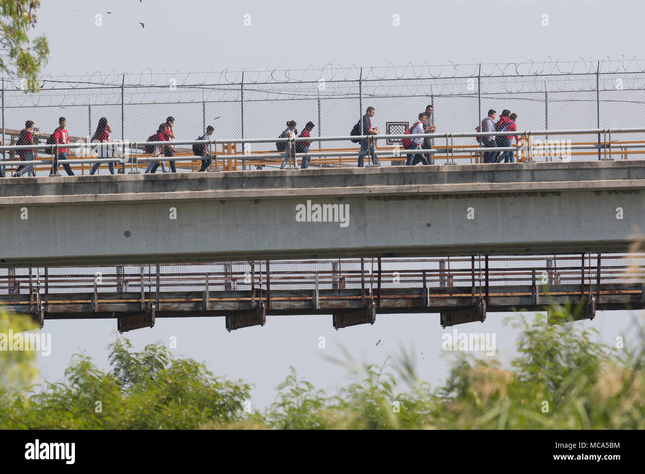 Students cross the international bridge headed to Mexico between Roma Texas and Ciudad Miguel Aleman at the end of the school day in the US. - Stock Image
