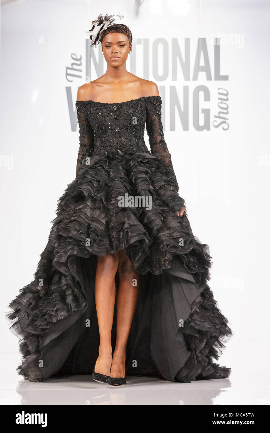 ExCel London, London, 14th April 2018. An unusual black dress shown by a model on the catwalk. The National Wedding Show takes place at ExCel London Exhibition Centre this weekend, showcasing the latest bridal trends, accessories, dresses and everything around planning the perfect wedding. Credit: Imageplotter News and Sports/Alamy Live News Stock Photo