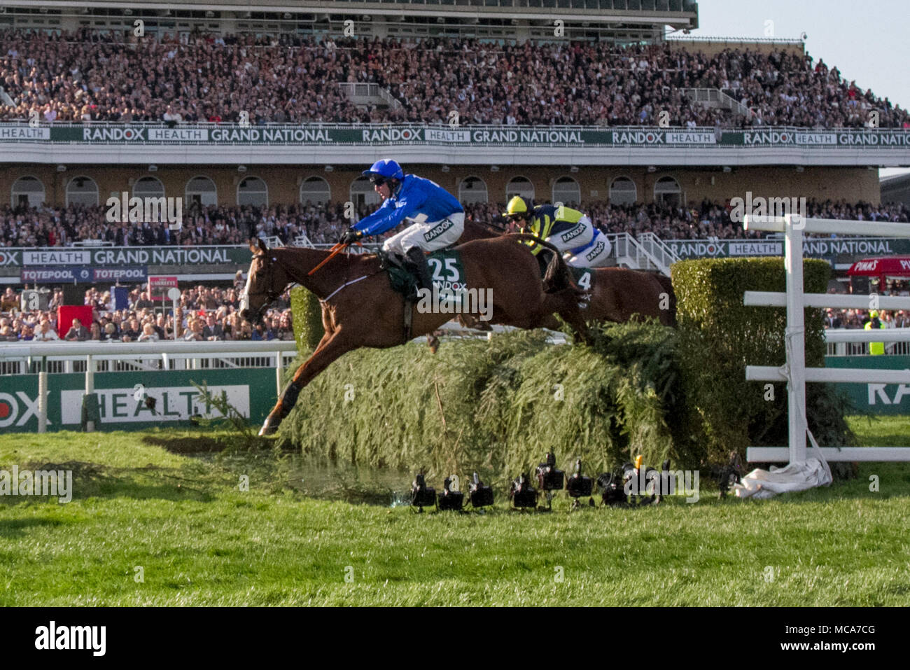 Randox Health Grand National, Aintree, Liverpool, Merseyside. 14th April 2018. Grand National horses & riders race over the grandstand water jump.  Credit: Mediaworld Images/Alamy Live News Stock Photo