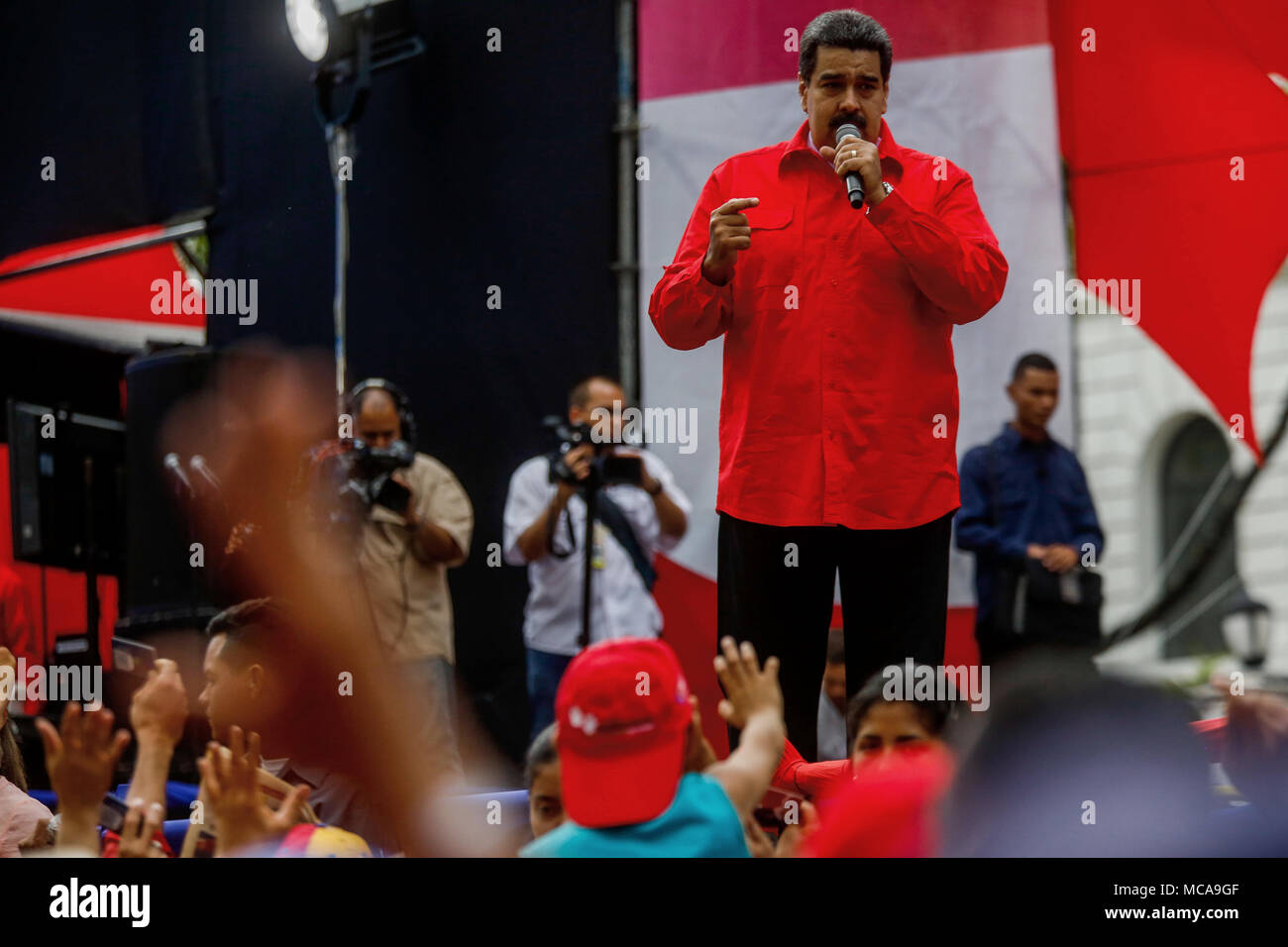 Caracas, Venezuela. 14th Apr, 2018. Venezuelan President Nicolás Maduro (c) speaks at a political event in Caracas, Venezuela, on 14 April 2018. Maduro called for peace and respect for Syria after condemning the attack by the United States, France and the United Kingdom against that country, and urged the governments of the world to demonstrate 'against war' and 'armamentism'. Credit: Cristian Hernández/EFE/Alamy Live News - Stock Image