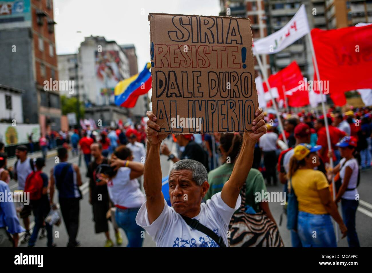 Caracas, Venezuela. 14th Apr, 2018. Supporters of Venezuelan President Nicolás Maduro participate in a political event in Caracas, Venezuela, on 14 April 2018. Maduro called for peace and respect for Syria after condemning the attack by the United States, France and the United Kingdom against that country, and urged the governments of the world to demonstrate 'against war' and 'armamentism'. Credit: Cristian Hernández/EFE/Alamy Live News - Stock Image