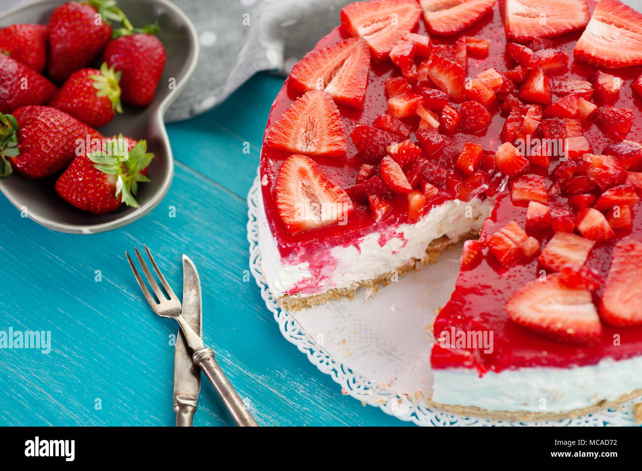 Homemade creamy dessert cake pie of red strawberry fresh fruit on blue wooden background with knife and fork - Stock Image