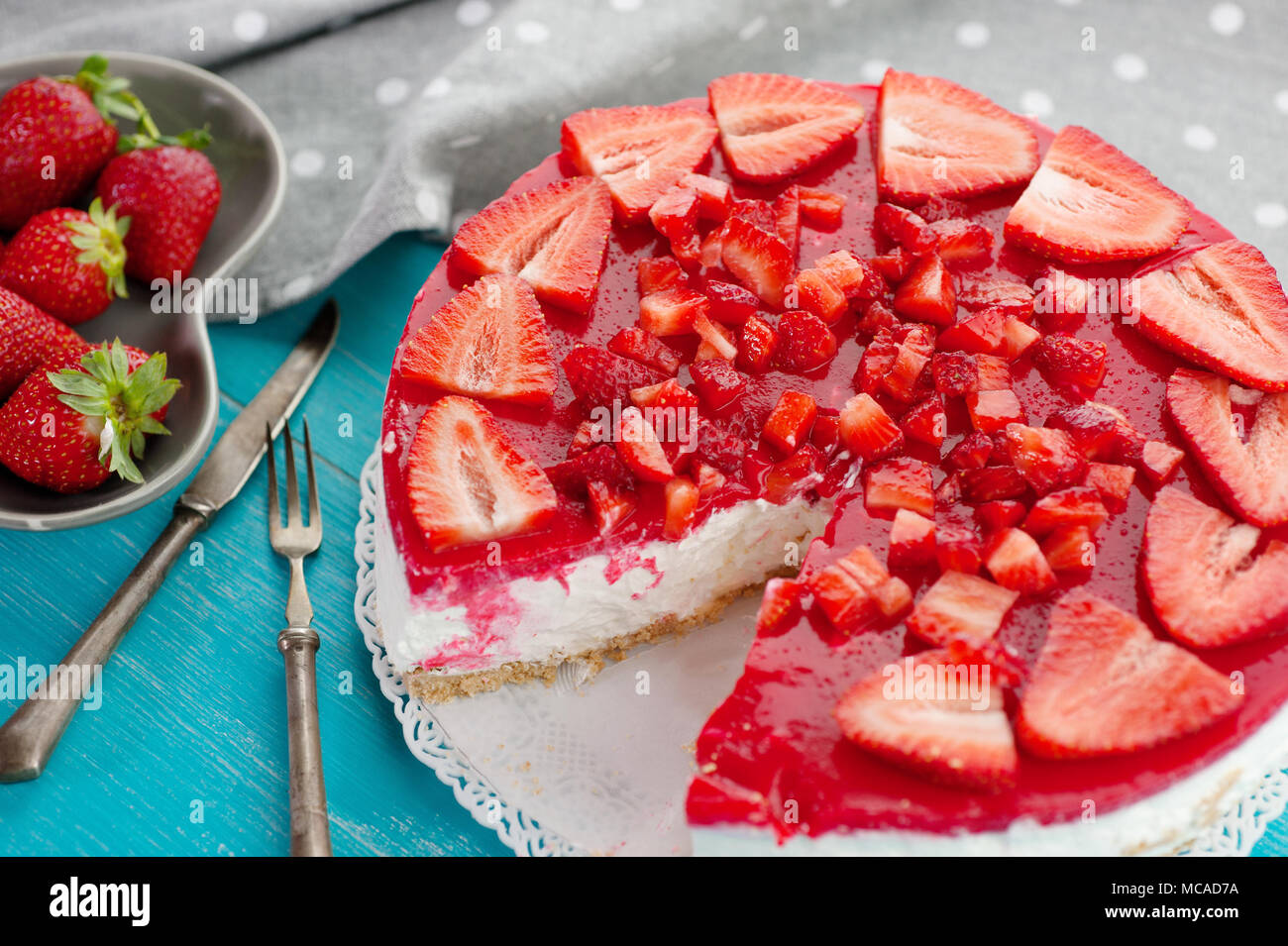 Dessert cake made with strawberry delicious red fruit on blue wooden background - Stock Image