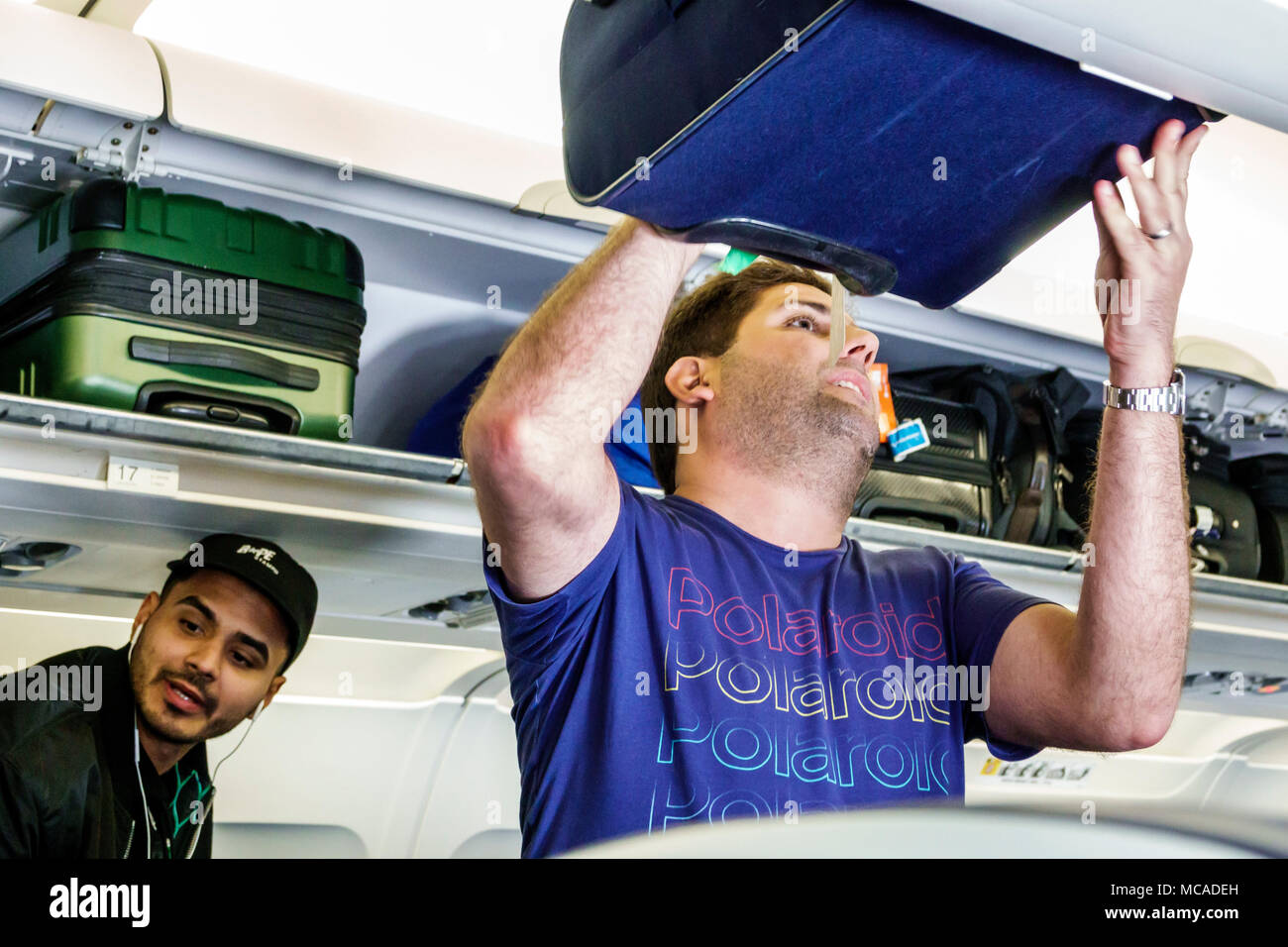 Florida Miami Miami International Airport MIA airplane cabin open overhead luggage bin Hispanic man passenger storing baggage - Stock Image