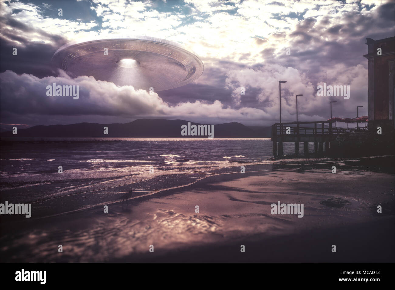 Alien spacecraft coming out of the clouds over the sea. - Stock Image