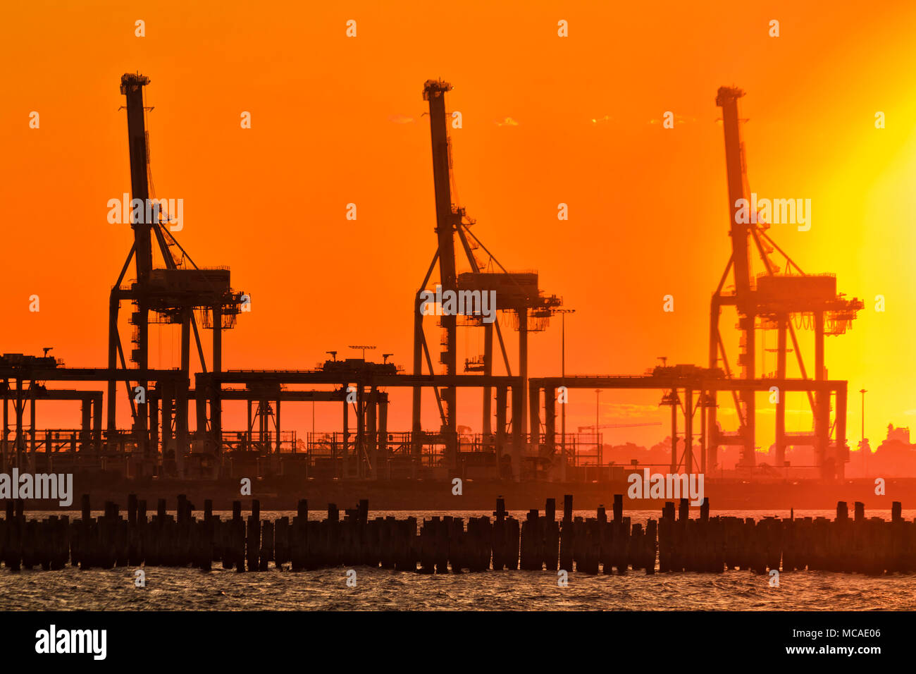Orange red burnt sky at sunset against setting hot sun contrasting tall heavy industrial cargo loading cranes in Port Melbourne over Port Phillip bay  - Stock Image
