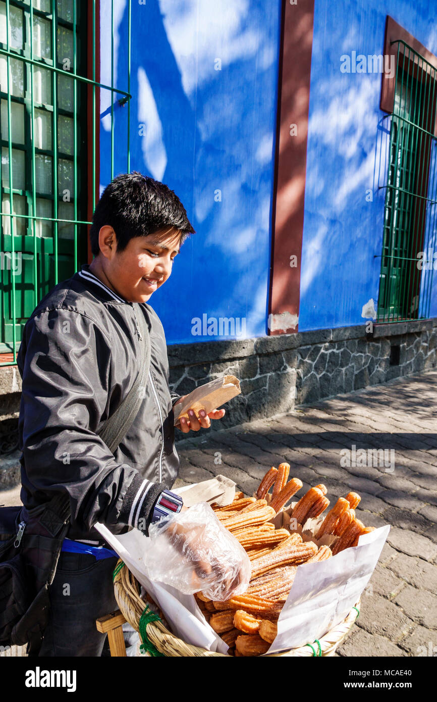 Mexico City Mexico Ciudad de Federal District Distrito DF D.F. CDMX Mexican Hispanic Coyoacan Del Carmen Museo Frida Kahlo museum Caza Azul Blue House exterior boy working sidewalk vendor churros North America American - Stock Image