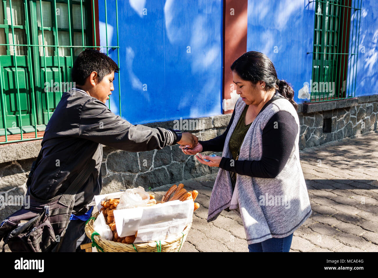 Mexico City Mexico Ciudad de Federal District Distrito DF D.F. CDMX Mexican Hispanic Coyoacan Del Carmen Museo Frida Kahlo museum Caza Azul Blue House exterior boy working sidewalk woman giving change vendor churros North America American - Stock Image