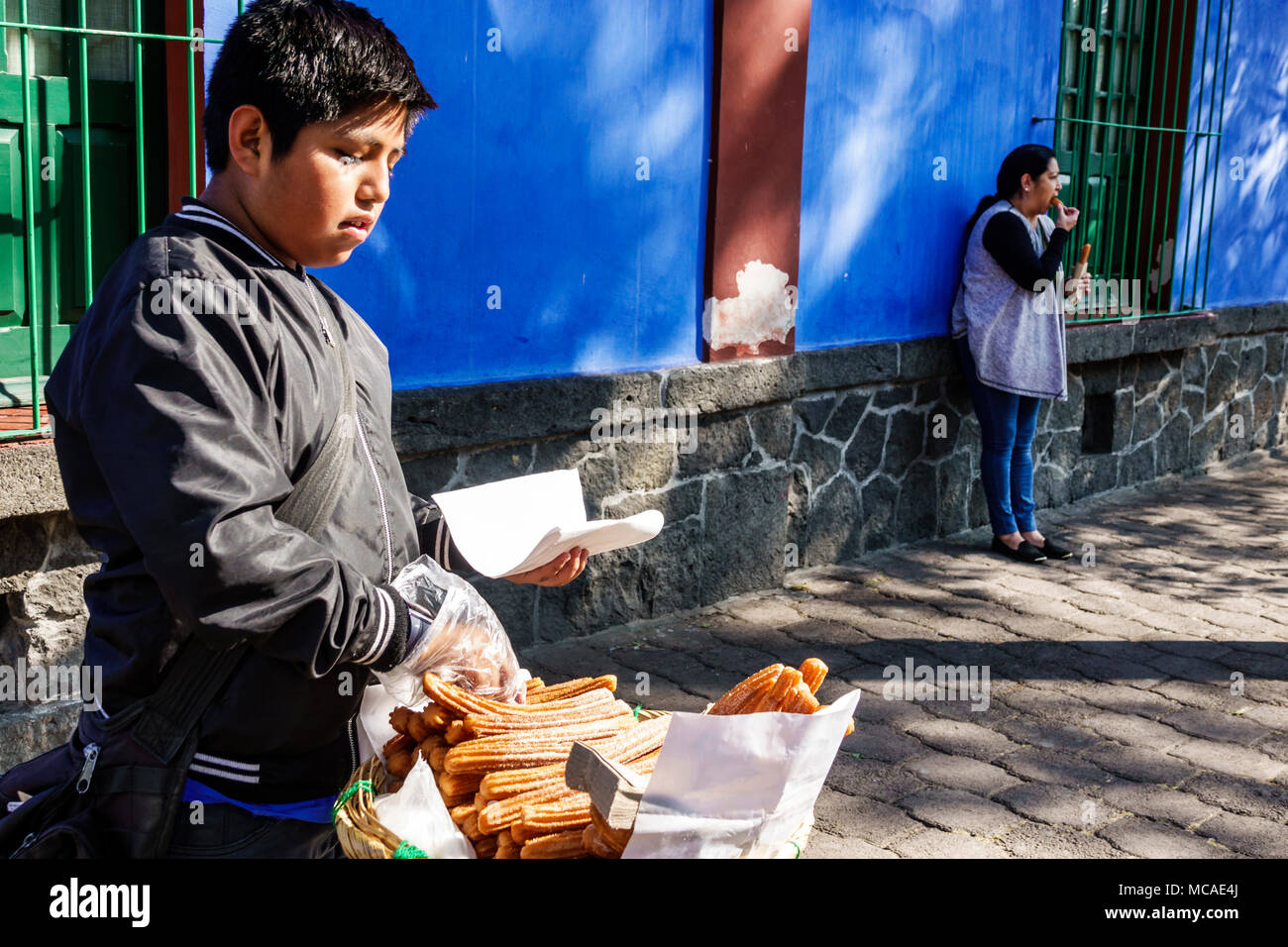Mexico City Mexico Ciudad de Federal District Distrito DF D.F. CDMX Mexican Hispanic Coyoacan Del Carmen Museo Frida Kahlo museum Caza Azul Blue House exterior boy working sidewalk vendor churros North America American - Stock Image