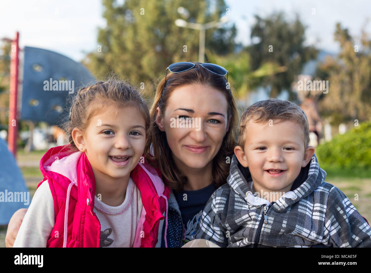 happy young mother with cute kids - smiling little daughter and son