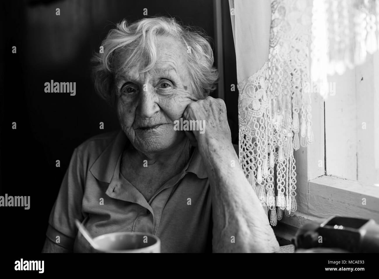 Portrait of elderly woman sitting at the table. - Stock Image