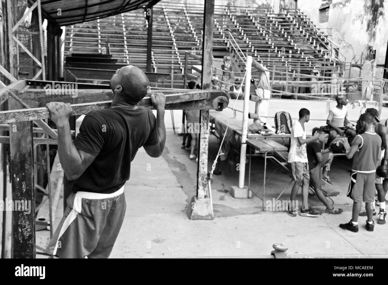 A black and white picture of a Cuban man with a black t-shirt doing a pull up in the boxing ring in Havana, July 2017 - Stock Image