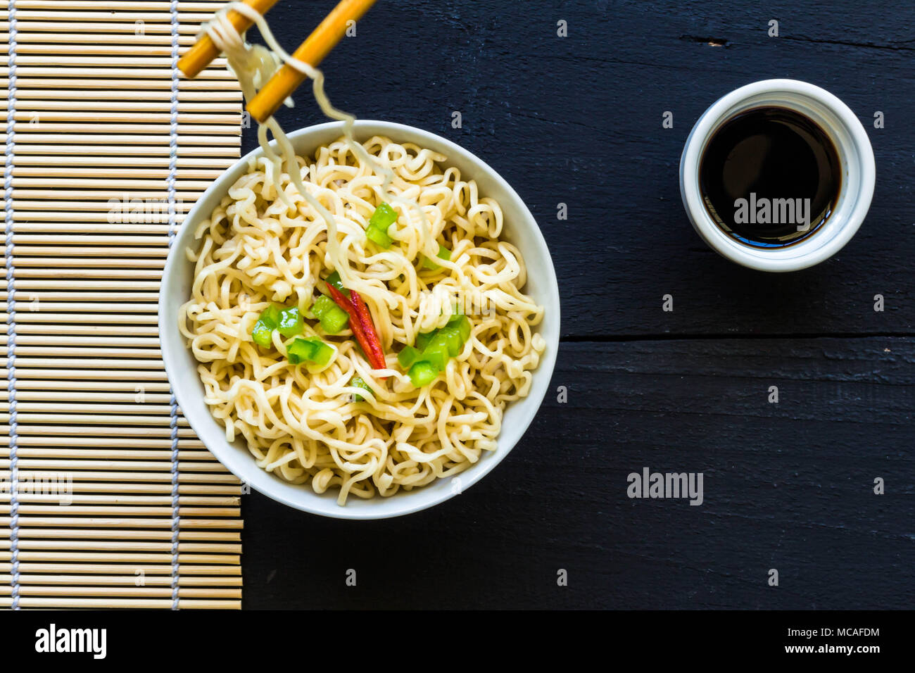 Bowl of instant cooked plain noodles with chopsticks and pepper garnish - Top view photo - Stock Image
