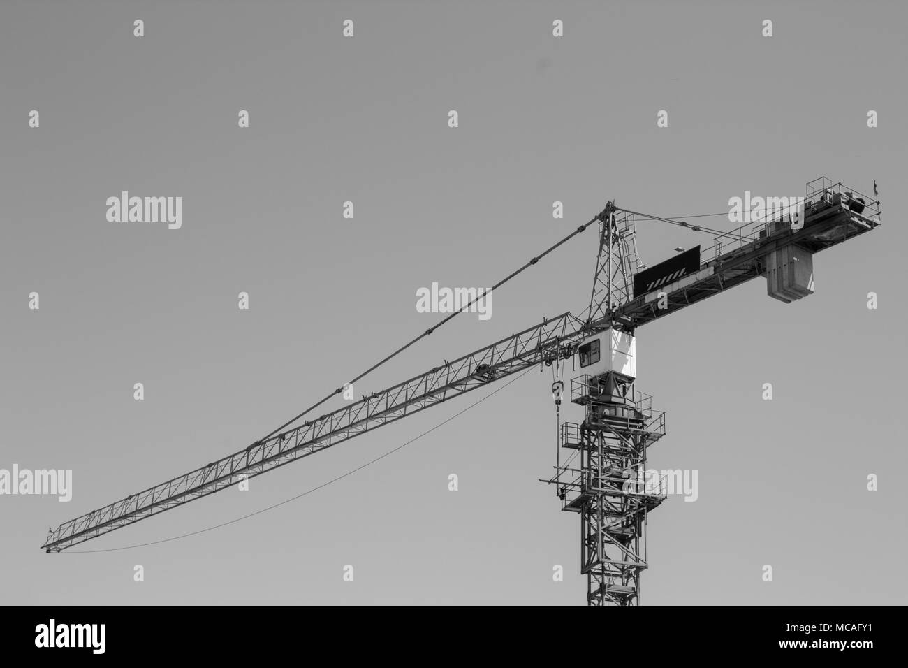 Photo of a construction crane in black and white. - Stock Image