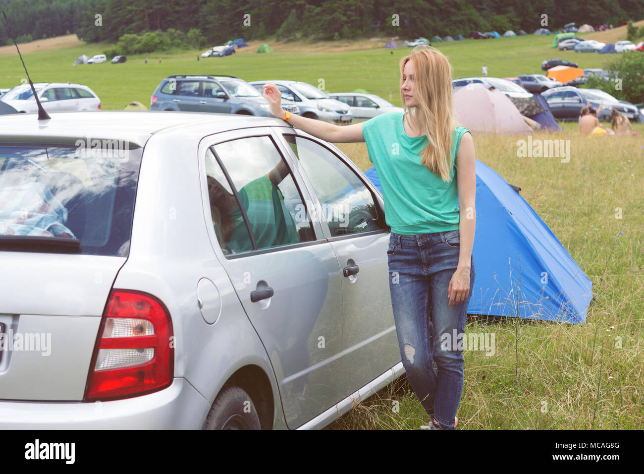 young woman leaning against car in camping area on open-air festival - Stock Image