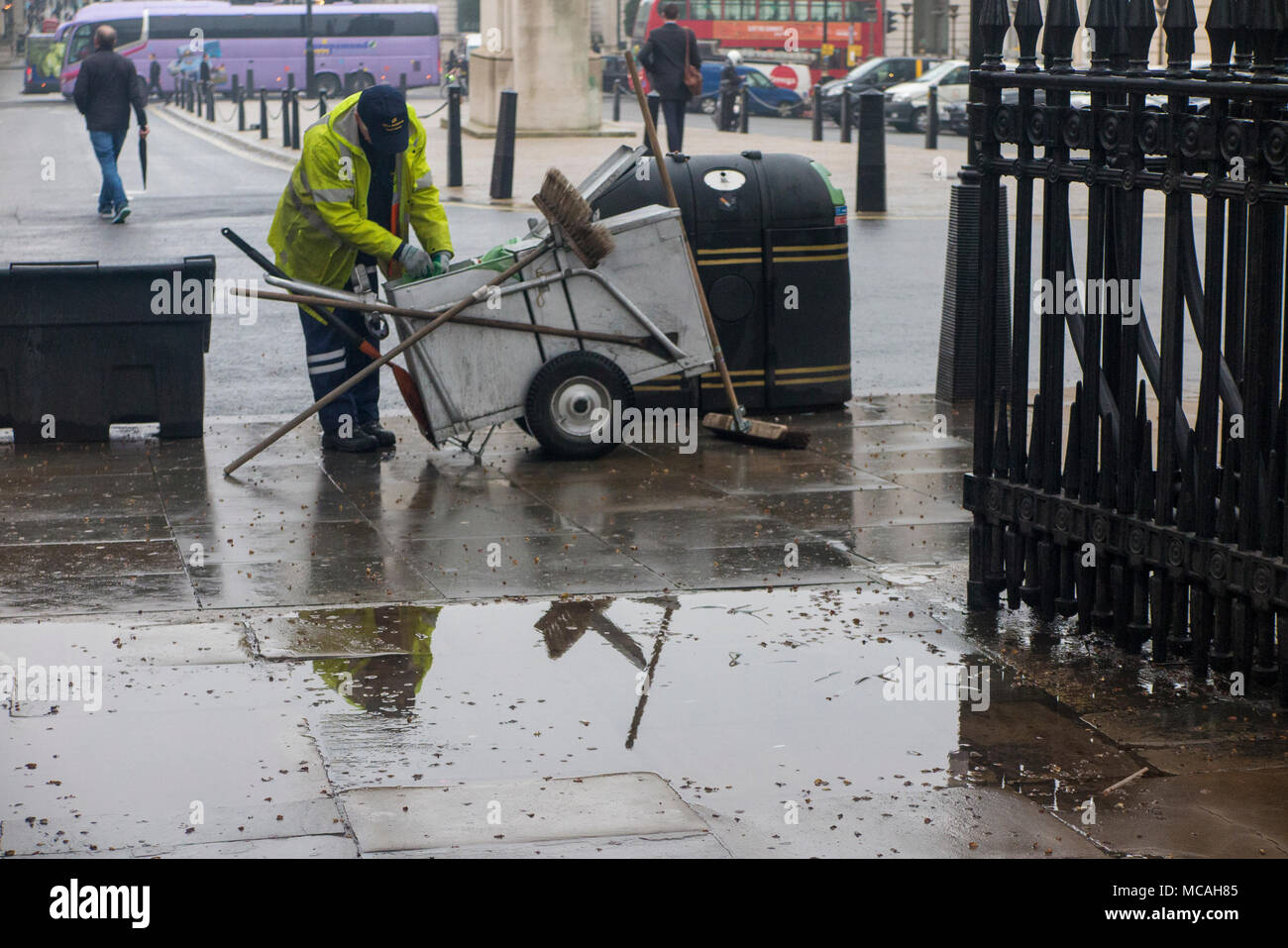 A street sweeper emptying a bin is reflected in a puddle on a rainy London street - Stock Image