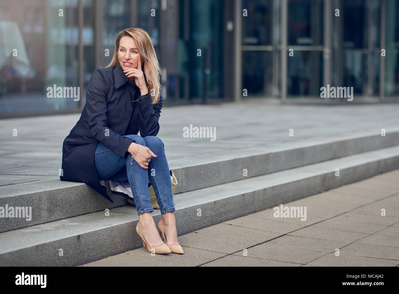 Attractive stylish woman in high heels and an overcoat sitting on urban steps looking thoughtfully to the side with her chin on her hand - Stock Image