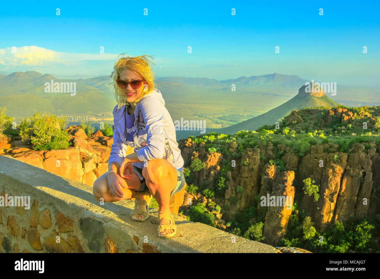Happy tourist sitting on the rocks after hiking at Valley of Desolation near Graaff-Reinet, South Africa.Sunset light. Blonde woman enjoying aerial views of Camdeboo National Park, Karoo, Eastern Cape - Stock Image