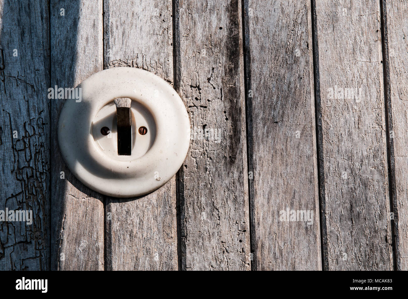 old electric light switch on a wooden wall Stock Photo