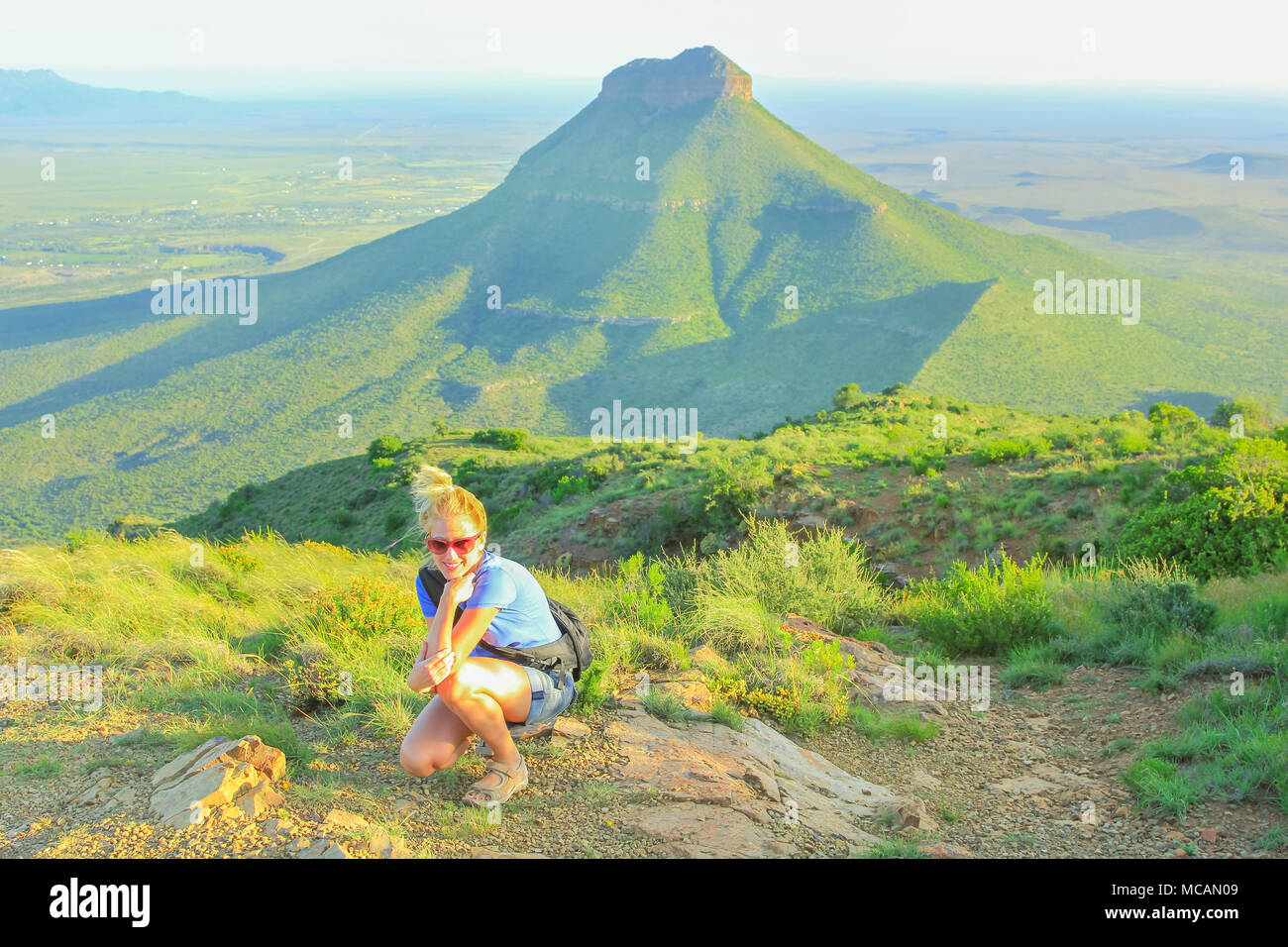 Happy tourist at Valley of Desolation near Graaff-Reinet, South Africa. Caucasian blonde woman enjoying in Camdeboo National Park, Karoo, Eastern Cape. Tour touristic in summer holidays. - Stock Image