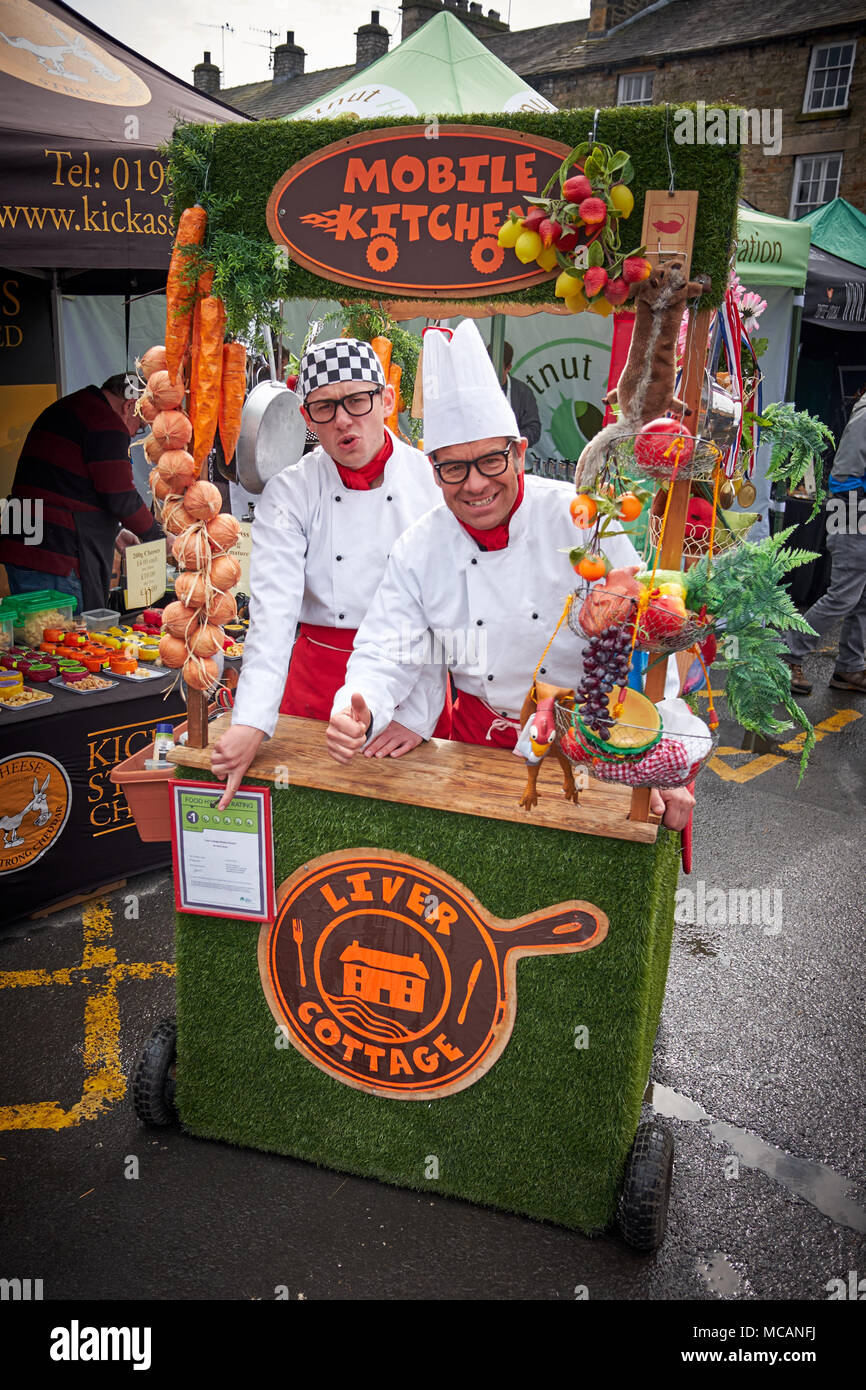 Kirkby Lonsdale, Cumbria / UK - April 15th 2018: Two men dress as chefs in a mobile kitchen at Taste Cumbria food festival in the market square. - Stock Image