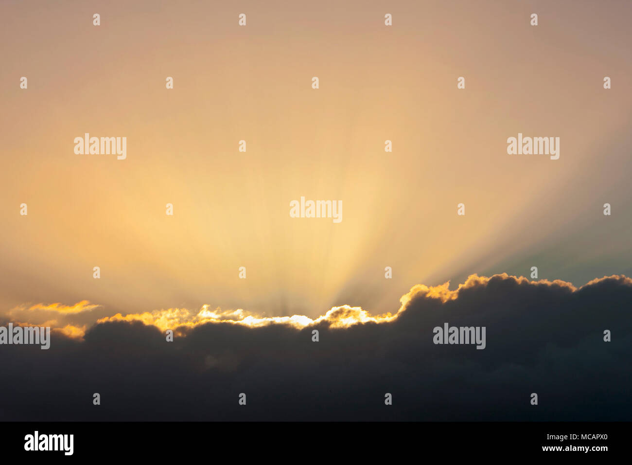 Golden sun beams emerging from behind a dark cloud at sunset - Stock Image