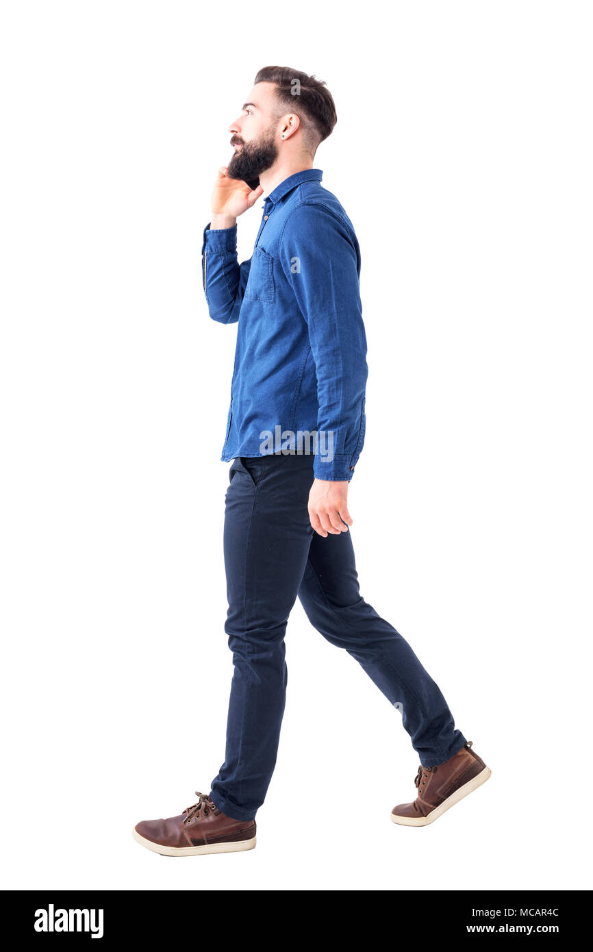 c55e5cd46437 Side view of confident busy businessman talk on the phone walking and  looking up. Full