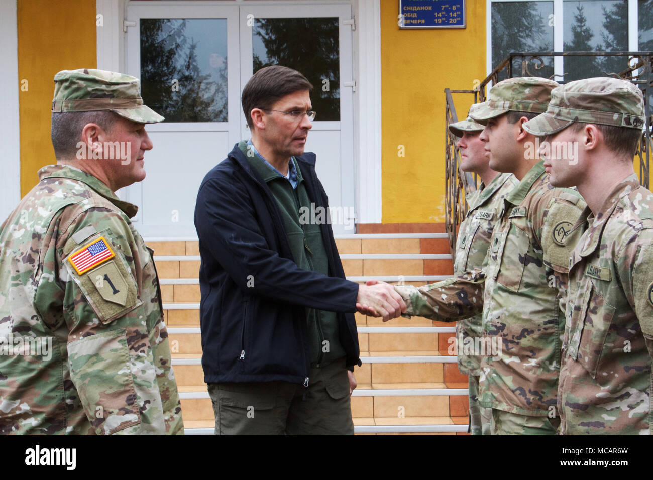 Yavoriv, Ukraine – Mark T. Esper, the United States Secretary of the Army presents a challenge coin to Spc. Kevin Morales, a motor transport operator assigned to the Joint Multinational Training Group – Ukraine during a visit to the Yavoriv Combat Training Center here Feb. 2. Currently more than 220 Soldiers from New York's 27th Infantry Brigade Combat Team are deployed to Ukraine where they are working hand-in-hand with the Ukrainian Army as they strive toward obtaining its goal of NATO interoperability. (U.S. Army photo by Sgt. Alexander Rector) Stock Photo