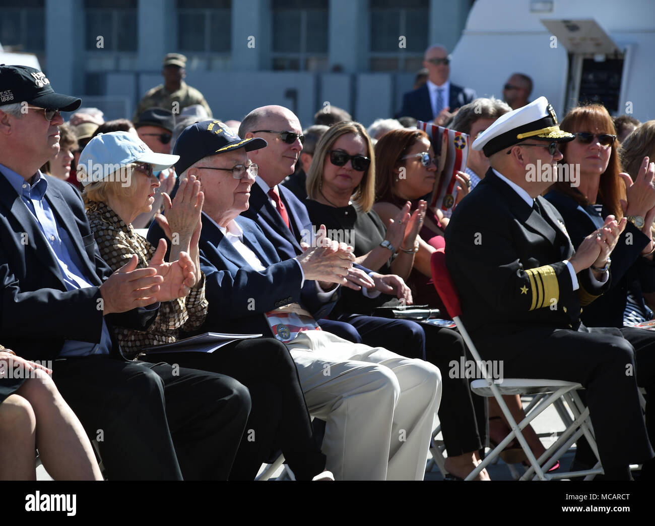 180203-N-RG360-0092 SAN DIEGO (Feb. 3, 2018) Warren Buffett, center, and his wife Astrid Menks, left of him, clap during the commissioning ceremony of the littoral combat ship USS Omaha (LCS 12) at Broadway Pier in downtown San Diego. Omaha is the 11th littoral combat ship to enter the fleet and the sixth of the Independence variant. The ship is named for the city of Omaha, Nebraska and is assigned to Naval Surface Forces, U.S. Pacific Fleet. (U.S. Navy photo by Mass Communication Specialist 1st Class Melissa K. Russell/Released) - Stock Image