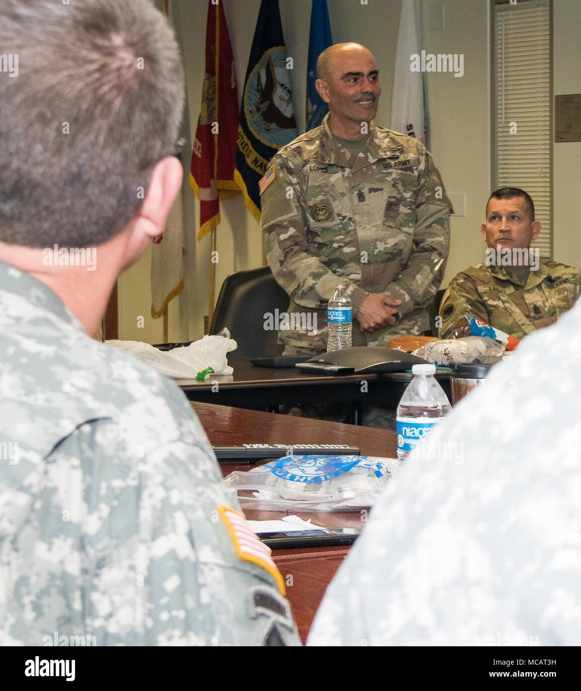 U.S. Army Command Sgt. Maj. Carlos O. Lopes, command sergeant major, 143d Sustainment Command (Expeditionary), speaks with battalion and brigade sergeants major and command sergeants major about their role in individual and collective training during a Mission Training Brief conducted Feb. 3, 2018, in Orlando, Fla. Lopes reminded his fellow sergeants major that they must coach and mentor noncommissioned officers so they may develop cohesive teams that have mastered the fundamentals of Pre-Combat Checks, Pre-Combat Inspections and Troop Leadership Procedures. (U.S. Army photo by Sgt. John L. Ca - Stock Image