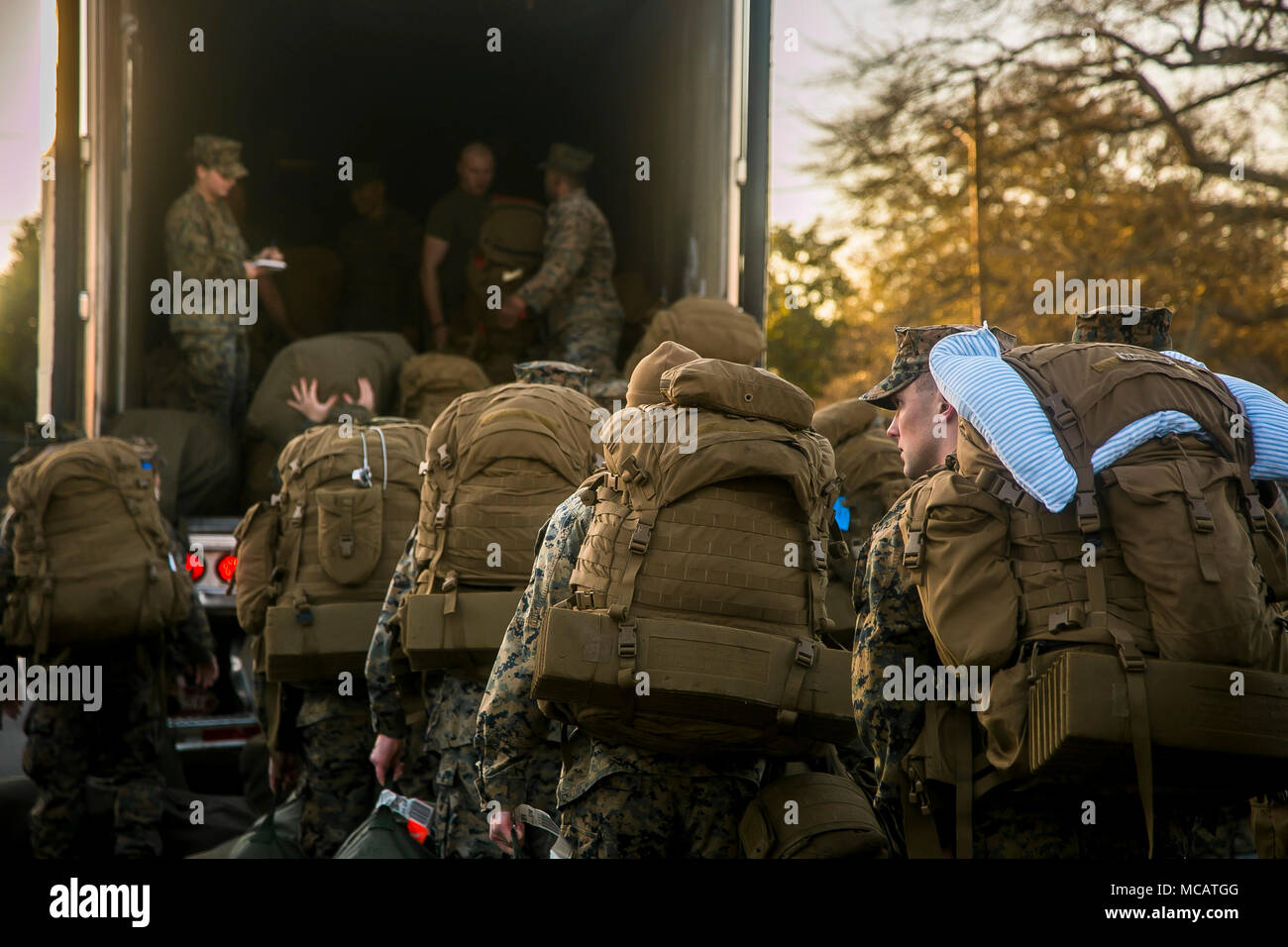 U.S. Marines and Sailors with the 26th Marine Expeditionary Unit (MEU) load their equipment onto a truck prior to departing Camp Lejeune, N.C., to embark on a deployment at sea Feb. 6, 2018. The MEU Marines and Sailors are deploying to support maritime security operations, crisis response and theater security cooperation, while also providing a forward expeditionary naval presence in Europe and the Middle East. - Stock Image