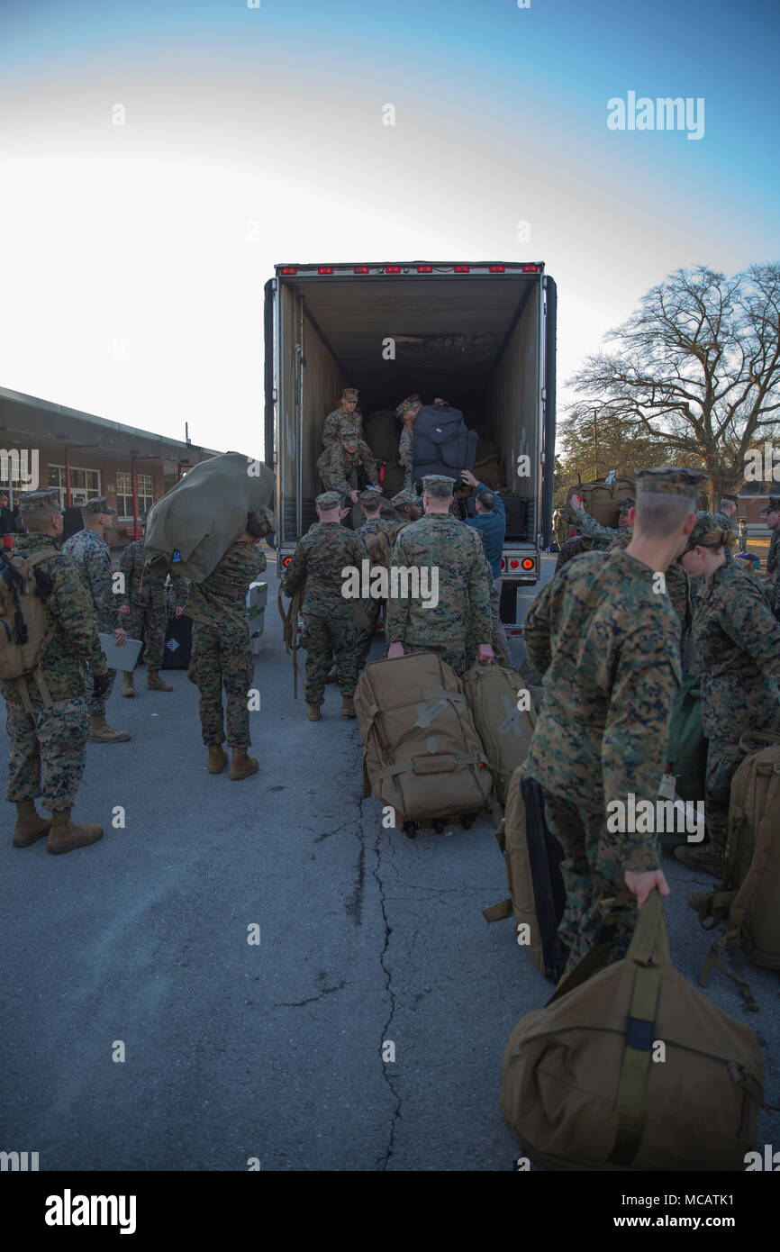 U.S. Marines and Sailors with the 26th Marine Expeditionary Unit (MEU) load equipment onto a truck during the unit's departure from Camp Lejeune, N.C., to embark on a deployment at sea Feb. 6, 2018. The MEU Marines and Sailors are deploying to support maritime security operations, crisis response and theater security cooperation, while also providing a forward expeditionary naval presence in Europe and the Middle East. (U.S. Marine Corps photo by Cpl. Austin Livingston) - Stock Image