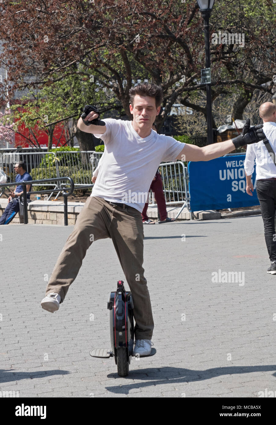 An Englishman living in New York riding an electric unicycle in Union Square Park in Manhattan, New York City. Stock Photo