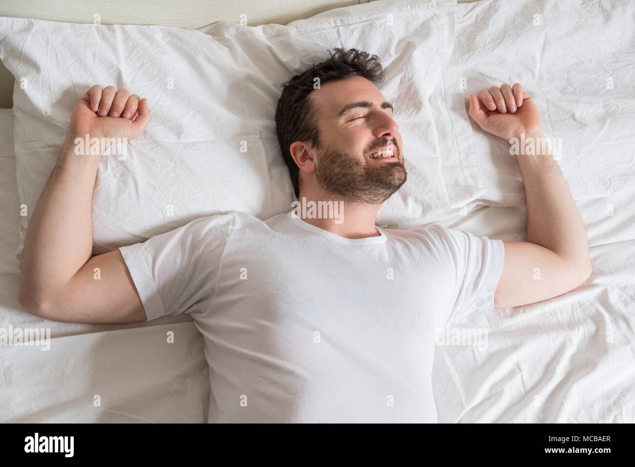 Top view of handsome man smiling while sleeping in his bed at home - Stock Image