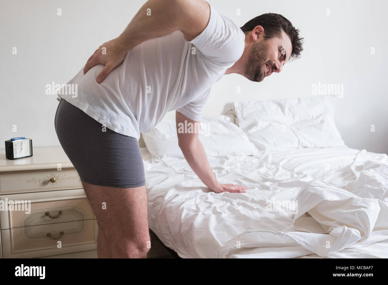 Man suffering from backache getting out of bed - Stock Image