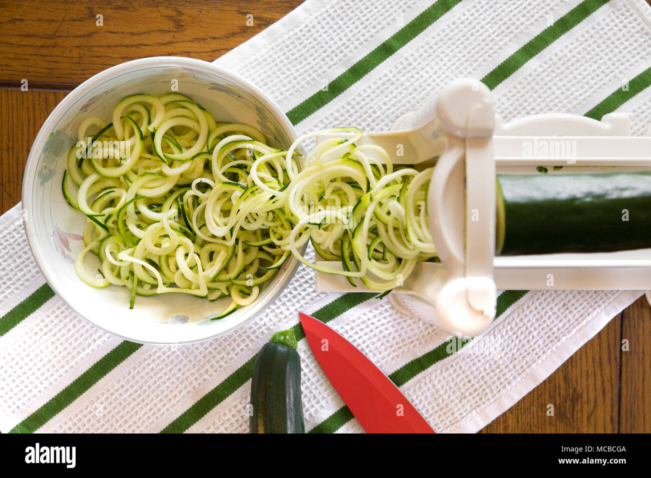 Spiral zucchini noodles called zoodles prepared in spiralizer kitchen gadget - Stock Image