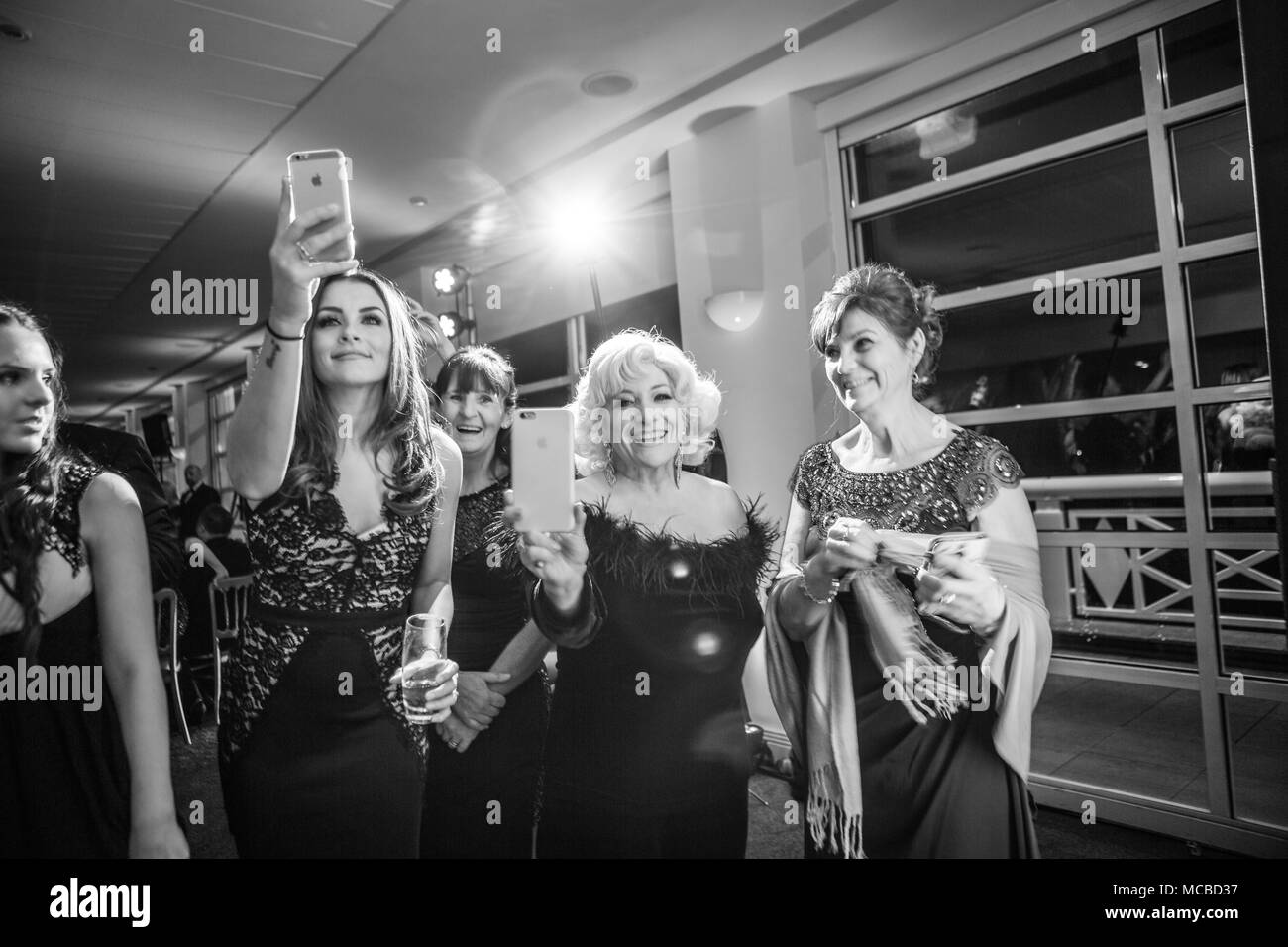 Group of mixed age ladies taking pictures on phones at a party in b;ack and white - Stock Image
