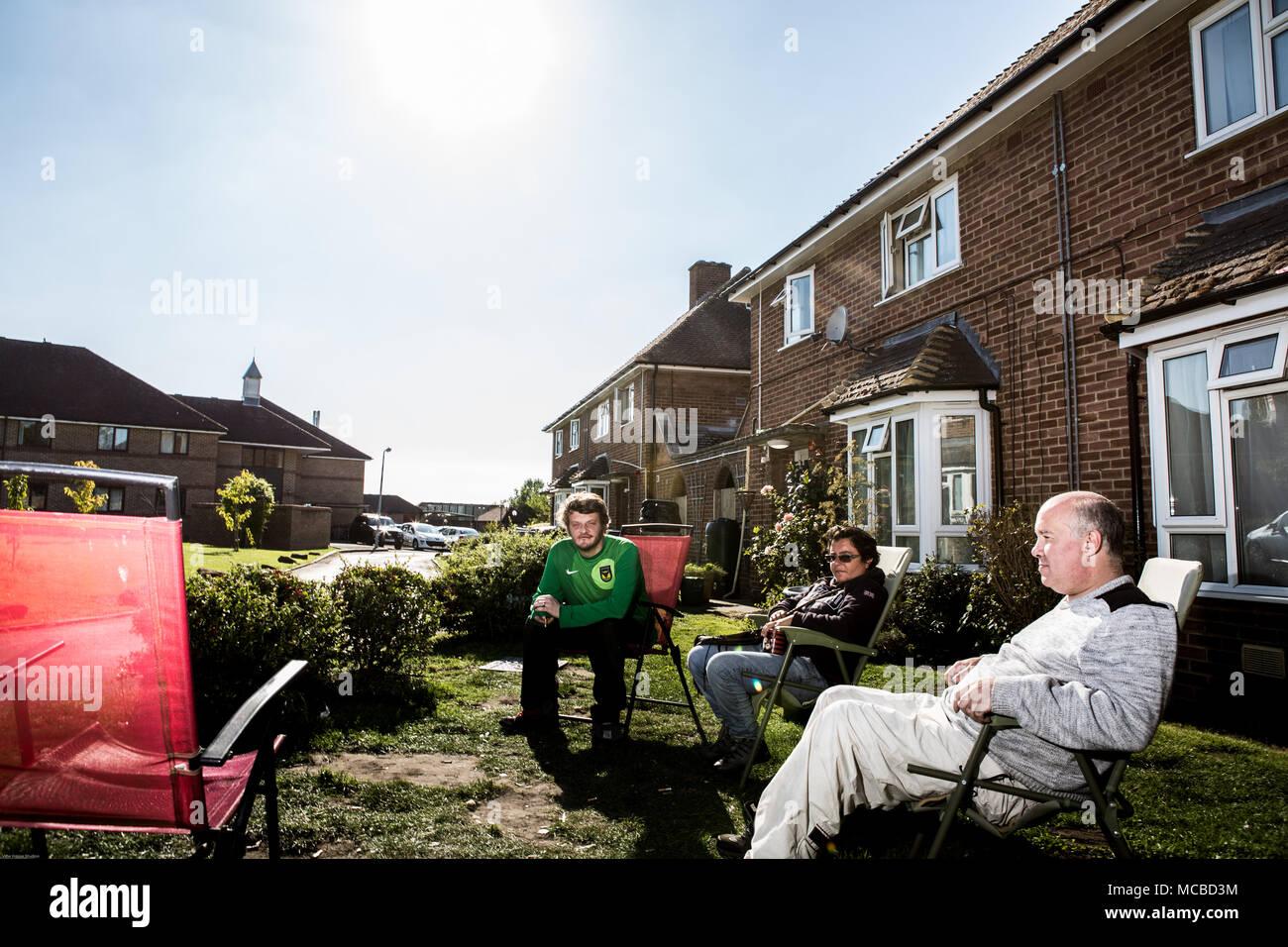 Group of residents sitting outside on social housing estate - Stock Image