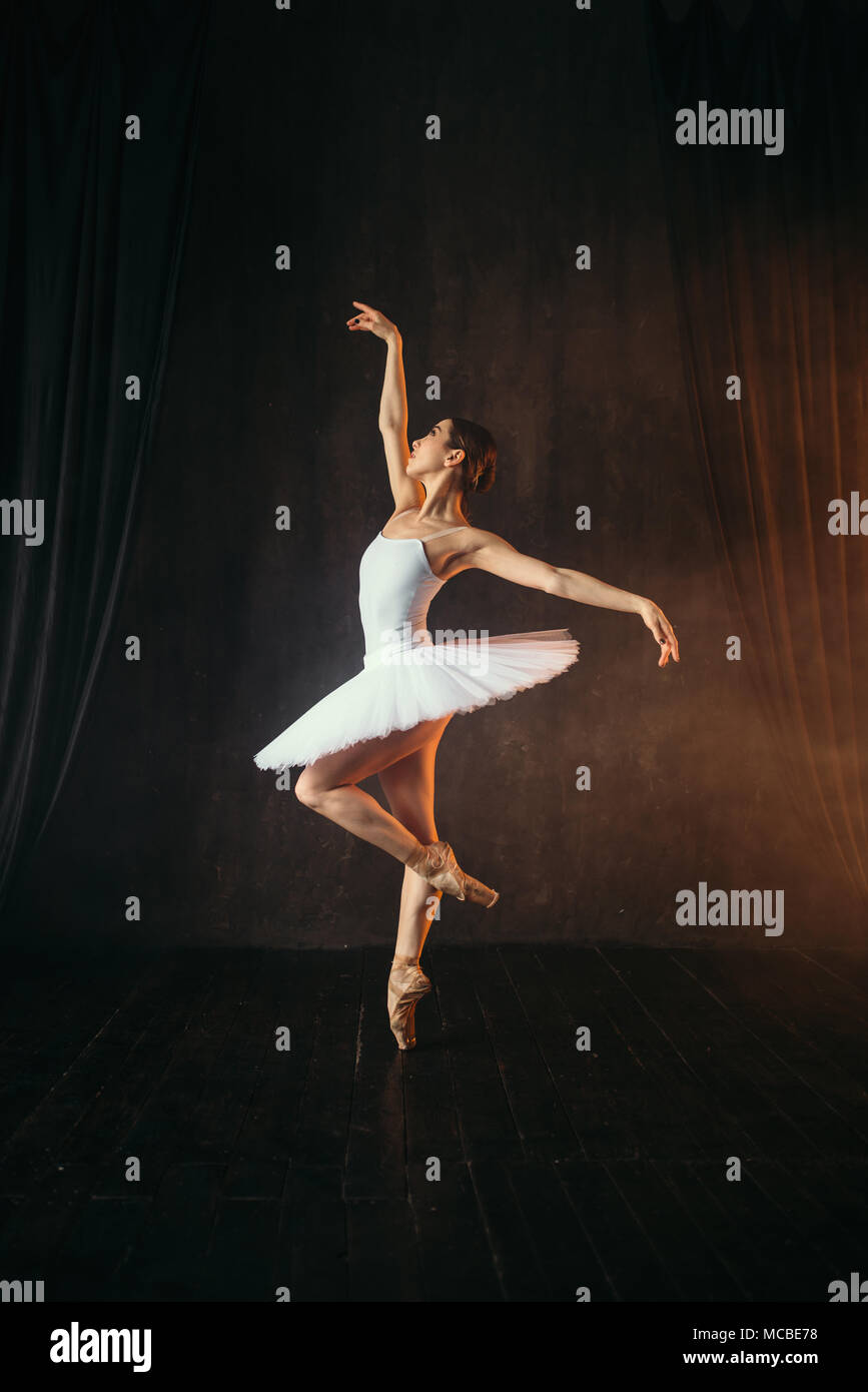 Ballerina in white dress and pointe shoes dancing - Stock Image
