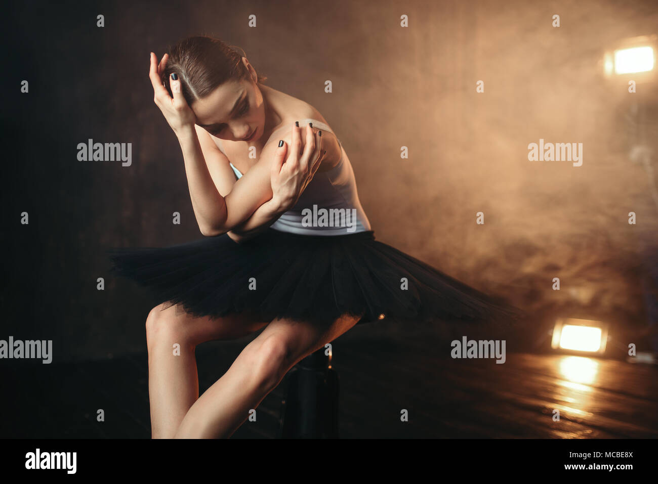 Ballerina sitting on black banquette in theatre - Stock Image