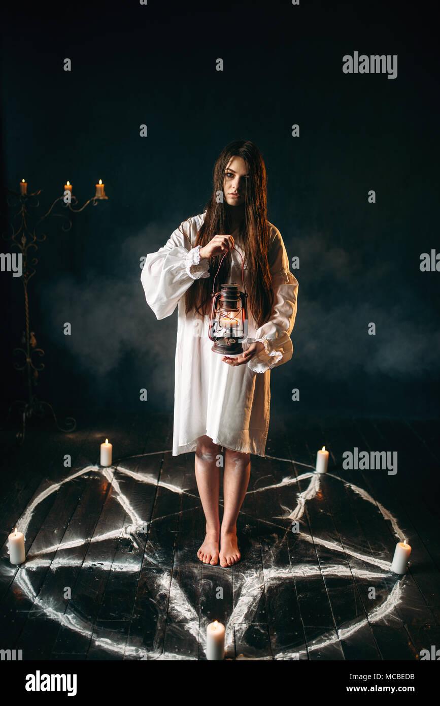 Woman holds kerosene lamp, pentagram circle, magic - Stock Image