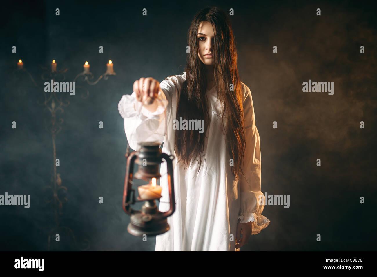 Female person holds kerosene lamp, dark magic - Stock Image